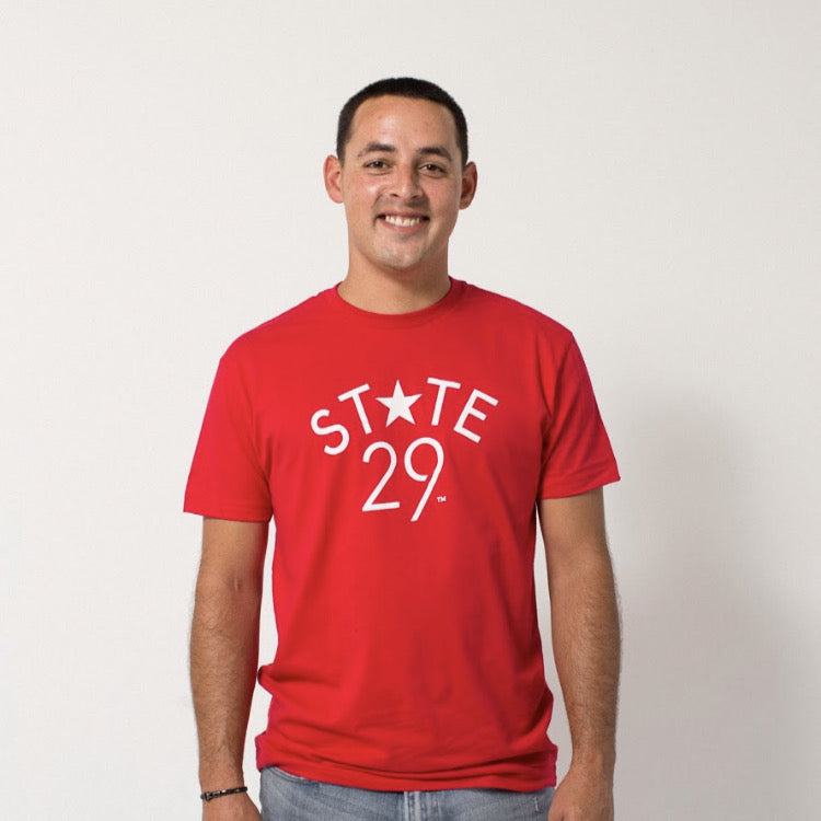 young male wearing a red tee with the 29th state apparel logo in white on the front