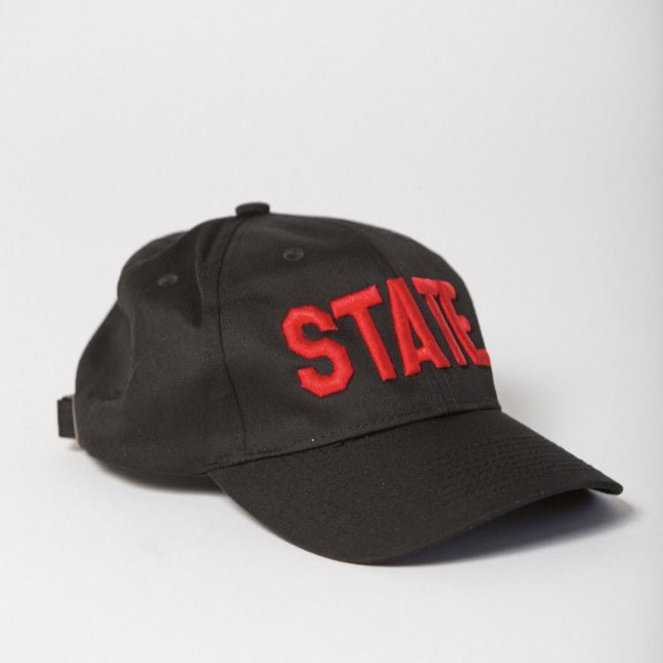 side view of black baseball hat with STATE embroidered on the front in red
