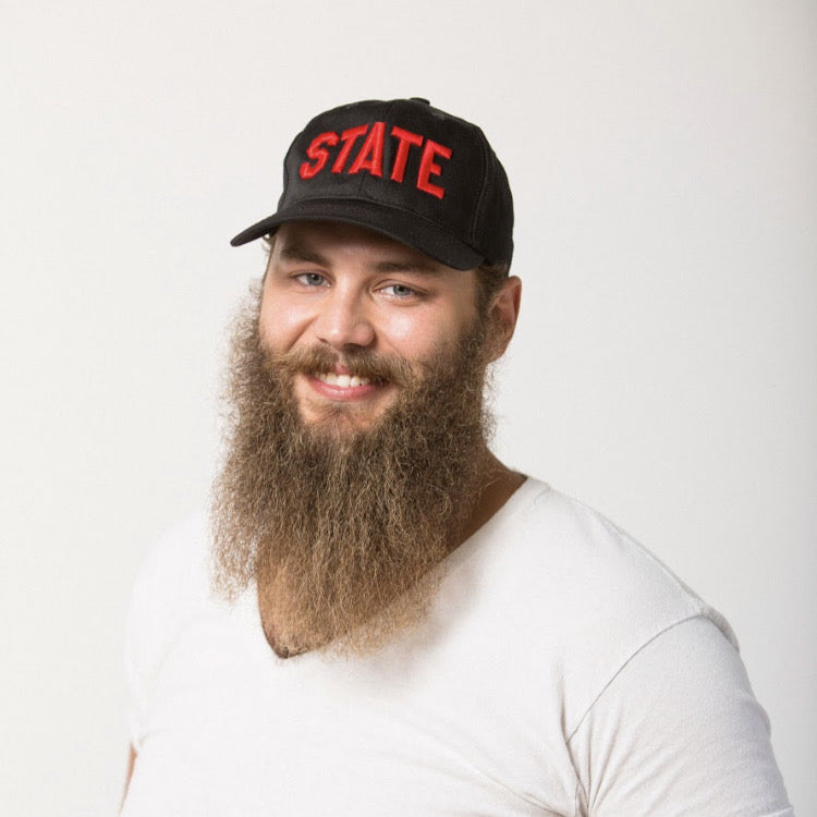 bearded male smiling in a black baseball hat with STATE embroidered in red on the front