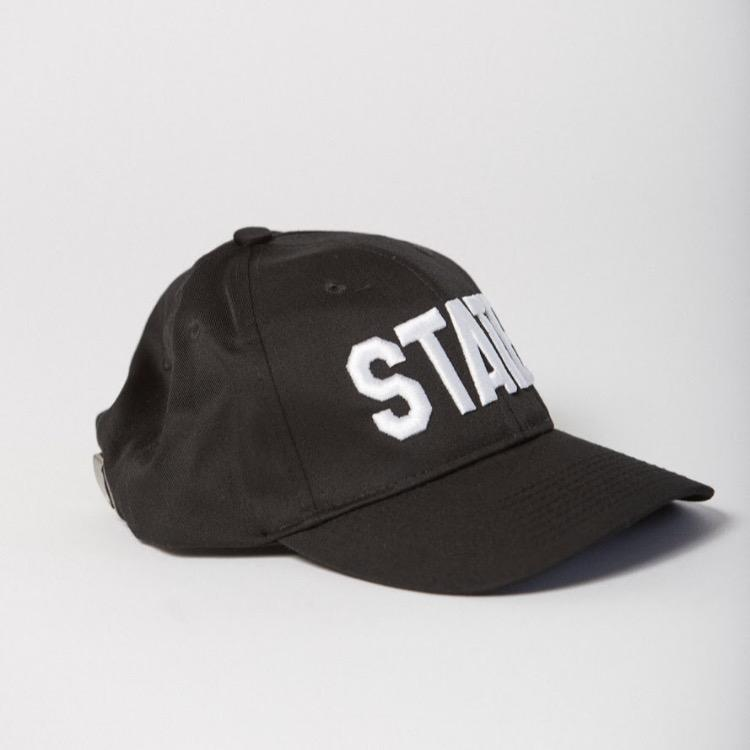 side view of black baseball hat with STATE embroidered on the front in white