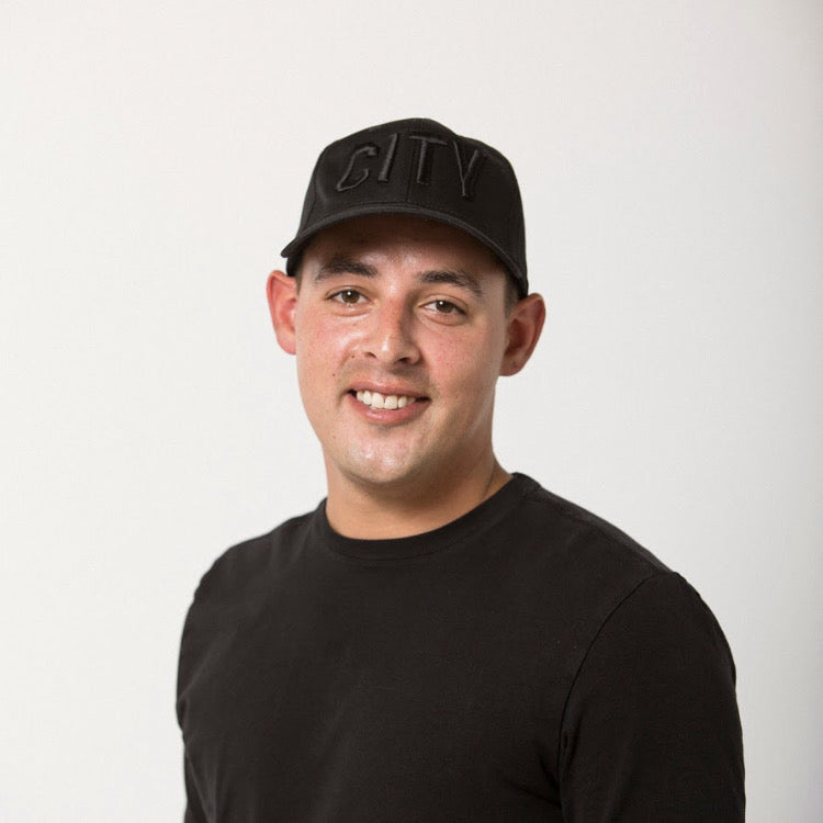dark haired young man in a black tee wearing a black on black CITY embroidered baseball hat