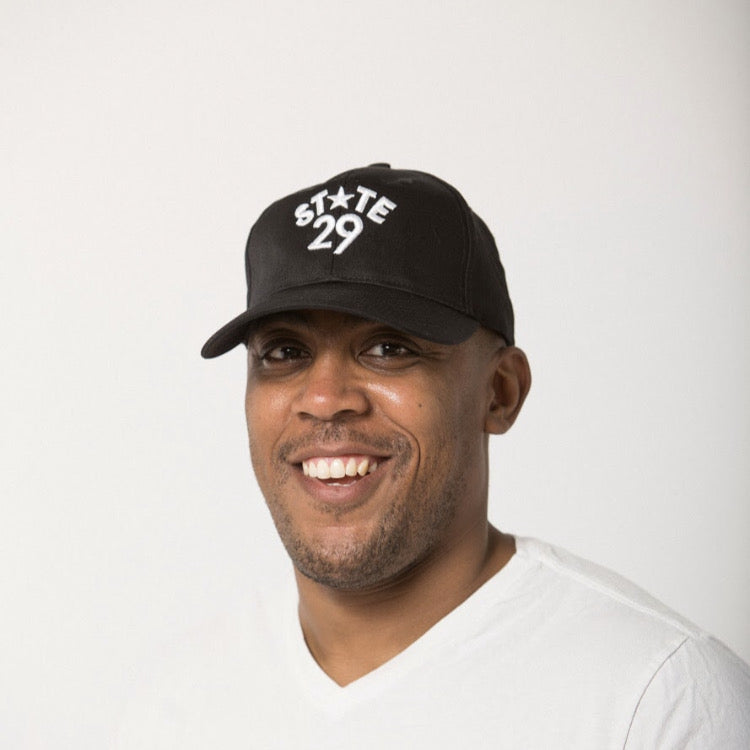 young man smiling in a white tee wearing a 29th state apparel logo baseball hat