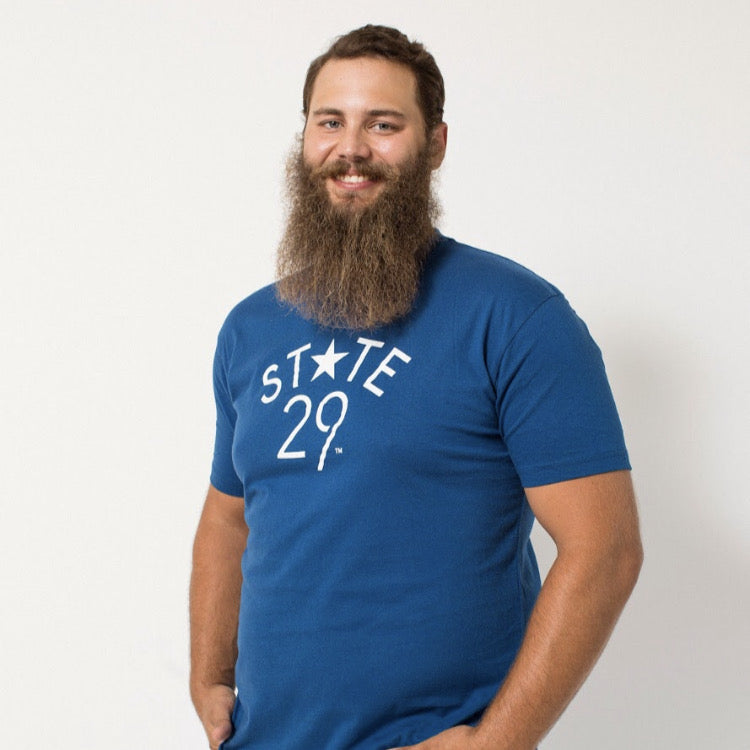 tall long bearded young man wearing a cool blue 29th state apparel logo tee