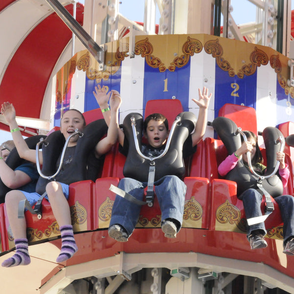 Child riding the Parachute Drop tower at ZDT's Amusement Park with his hands up