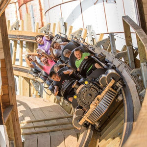Switchback Roller Coaster - Riders being launched through a building on a wooden shuttle roller coaster.
