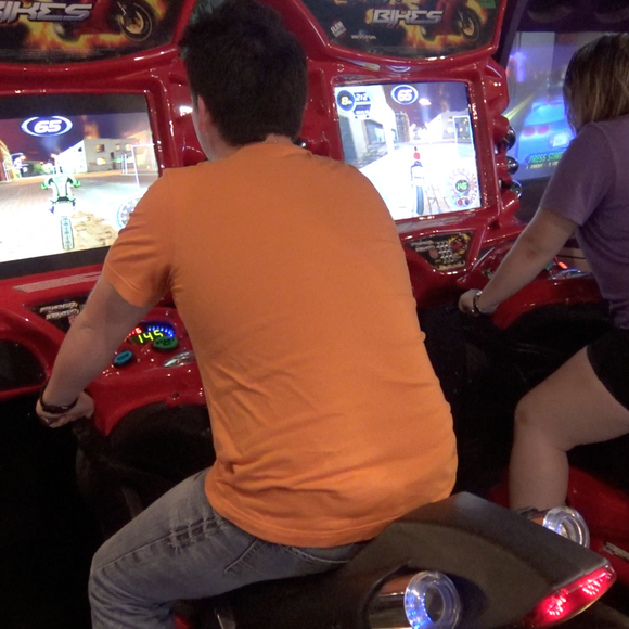 Video Game Arcade at ZDT's Amusement Park - Teenagers play Fast n Furious Super Bikes arcade game set on free play.