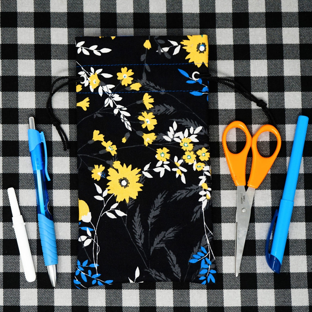 Black Floral Drawstring Bag surrounded by Accessories