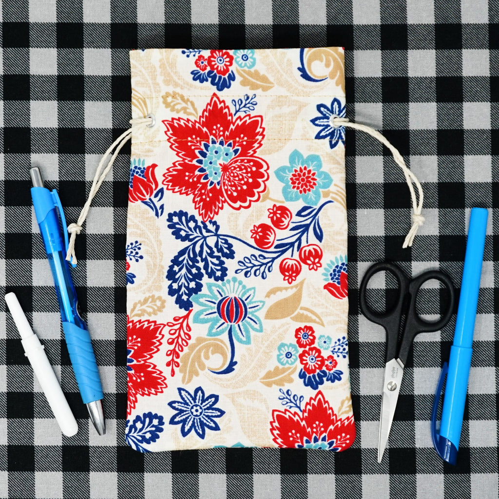 red and blue floral drawstring bag surrounded by cross stitch accessories