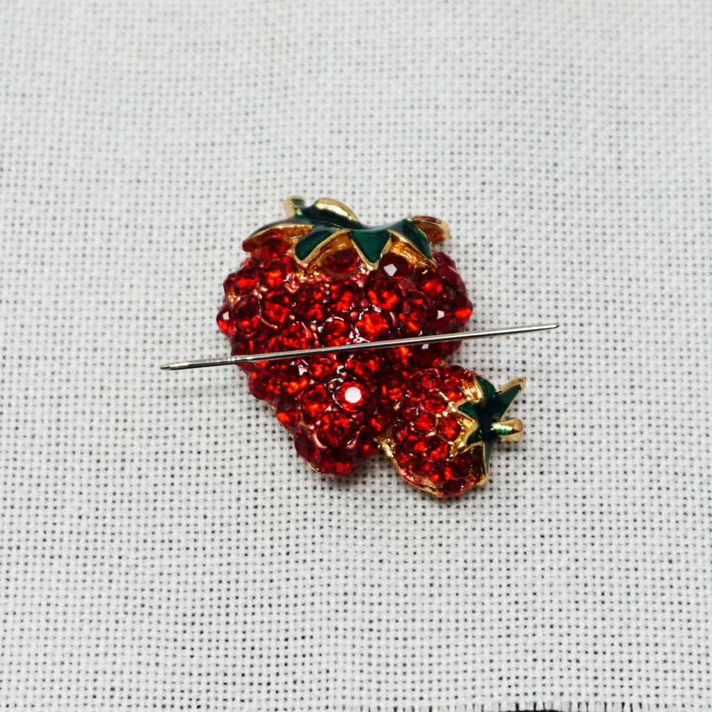 strawberry needle minder holding a needle by accoutrement designs