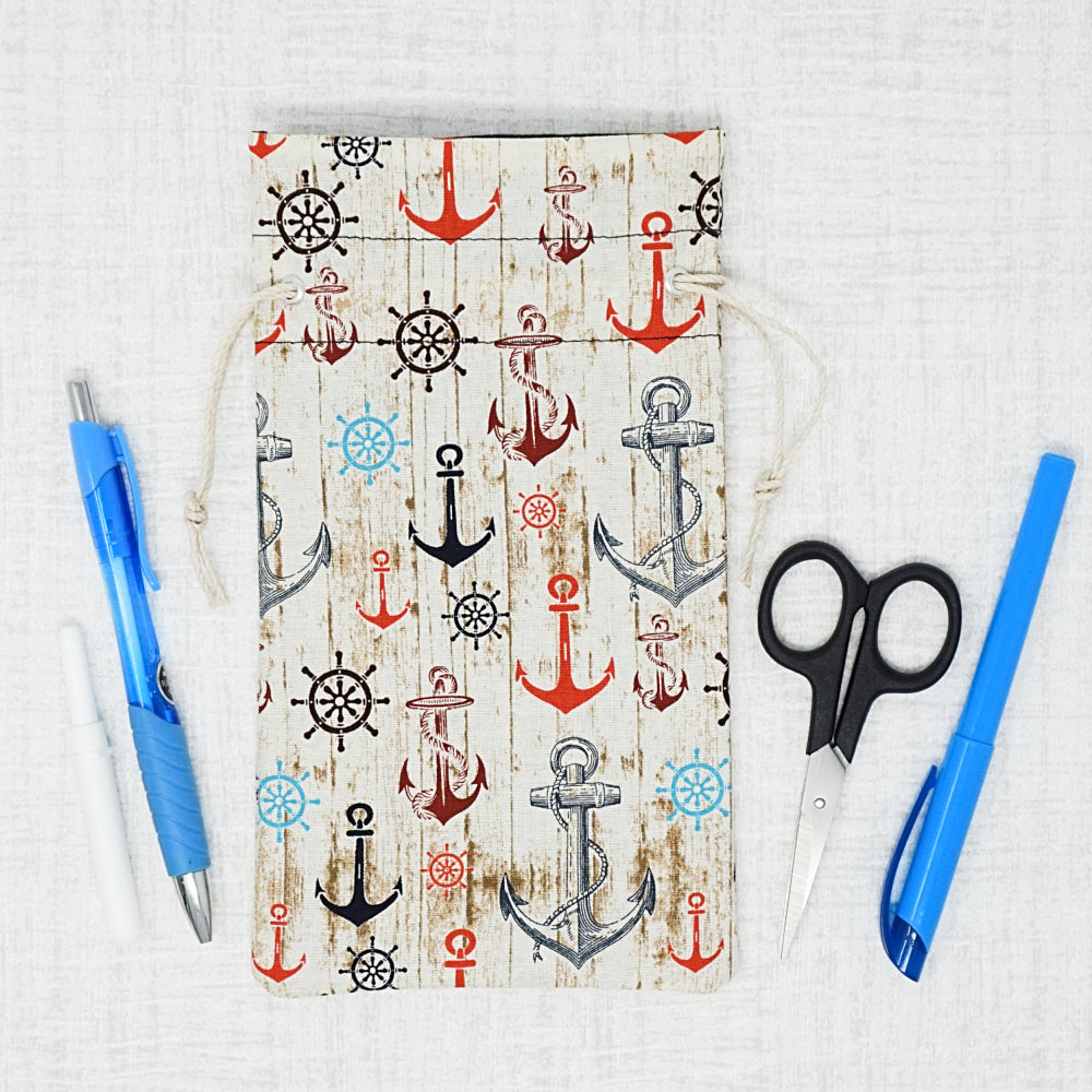 Anchor cross stitch drawstring bag surrounded by accessories