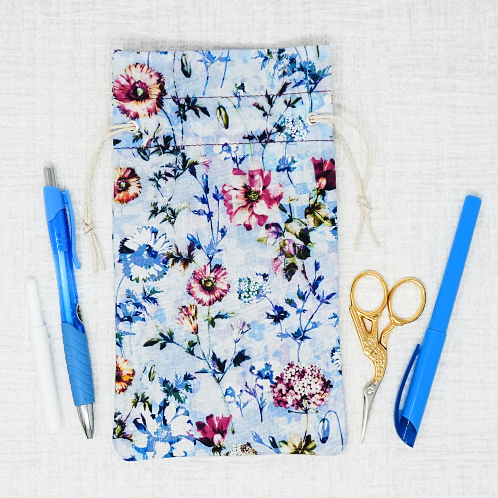 blue floral bag surrounded by accessories