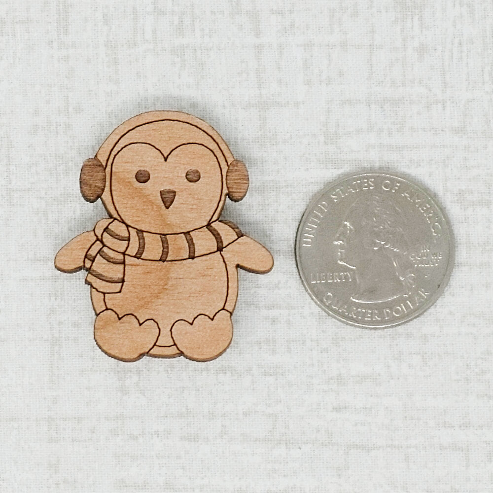 Dark wooden penguin needle minder next to a quarter