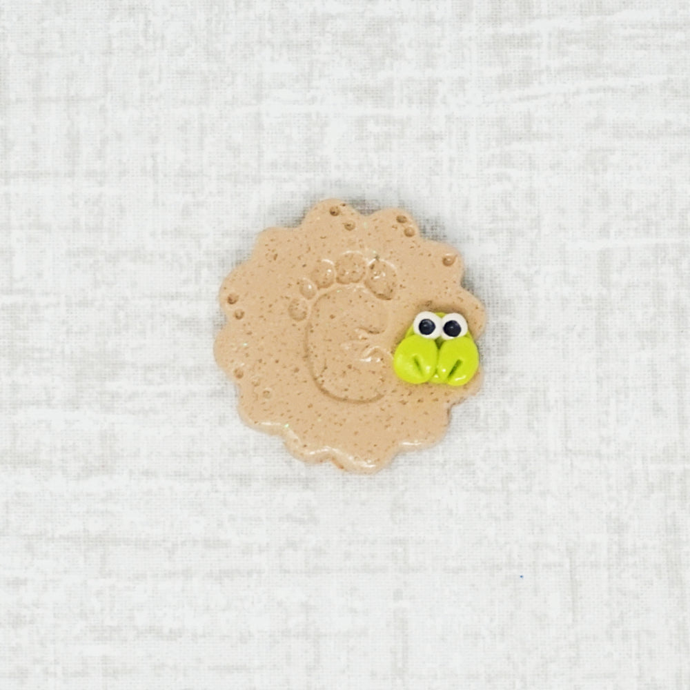 sandy footprint with a crab needle minder