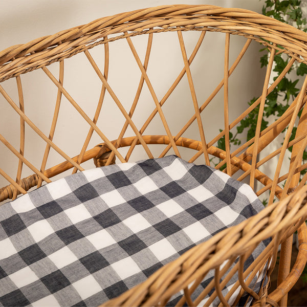 Navy and white large gingham check fitted bassinet sheet fitted on a natural cane bassinet