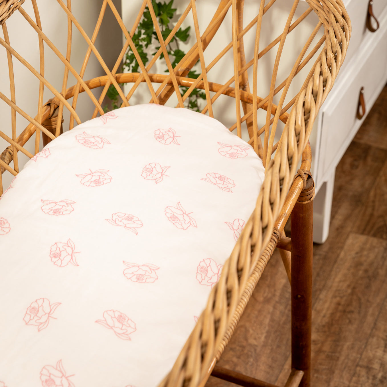 Organic cotton bassinet sheet fitted on a natural cane bassinet