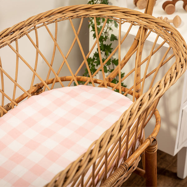 Pink and white gingham check bassinet sheet fitted on a natural cane bassinet