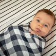 Baby swaddled in a navy gingham cotton muslin baby blanket