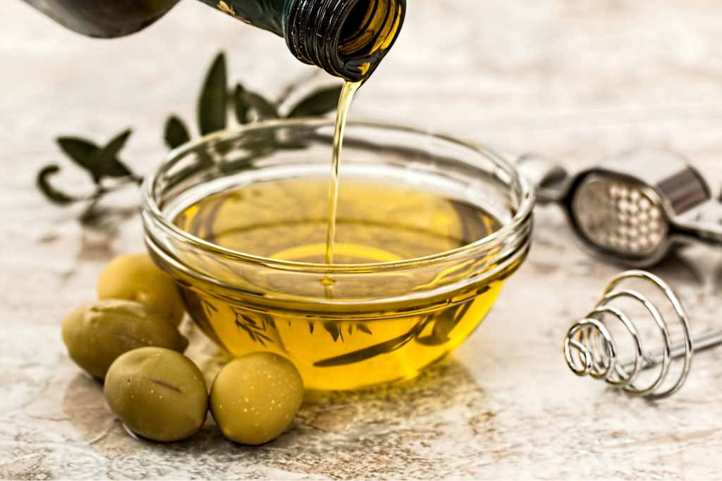 Extra virgin olive oil pouring into glass bowl