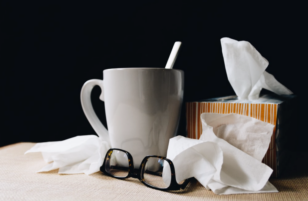Box of tissues, glasses and cup of warm ginger and lemon tea for the flu