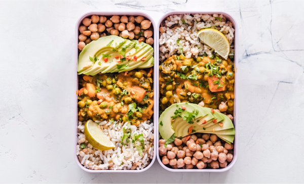 Lunchbox with chickpeas, curry, avocado slices, lemon wedge and rice