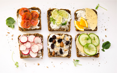 Slices of toast with tomato, radish slices, nuts, cucumber, cheese, sour cream