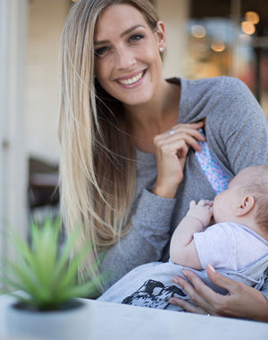 active mom breastfeeding in a gray crew neck maternity top