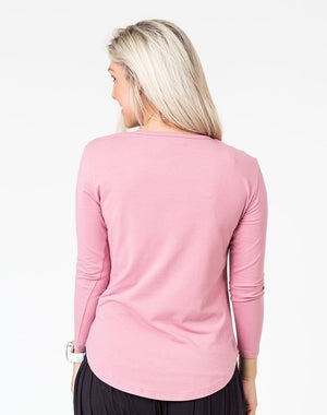 back view of a mom in a pink maternity top with long sleeves