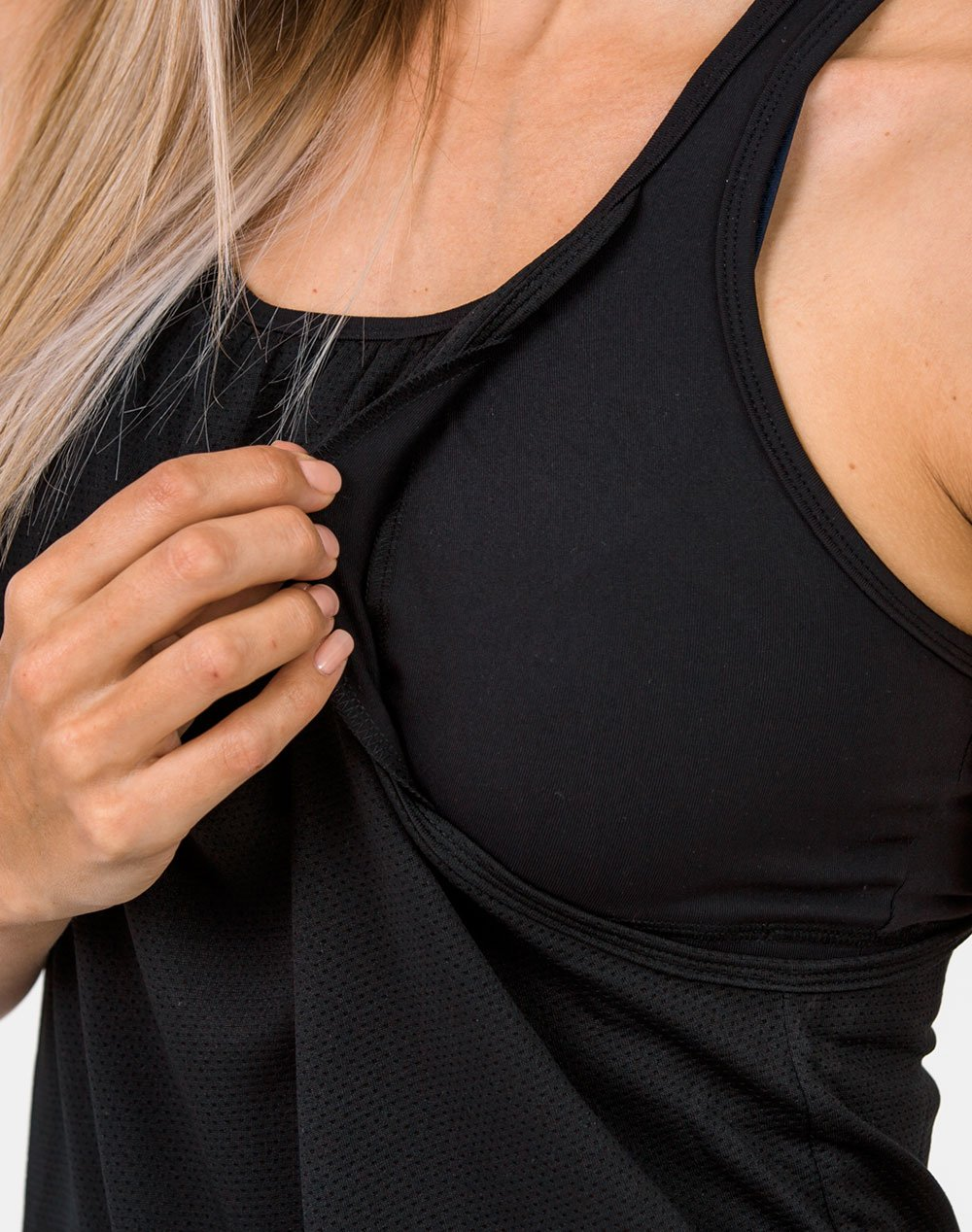 mom in a black breastfeeding top close up with the armhole pulled open to breastfeed
