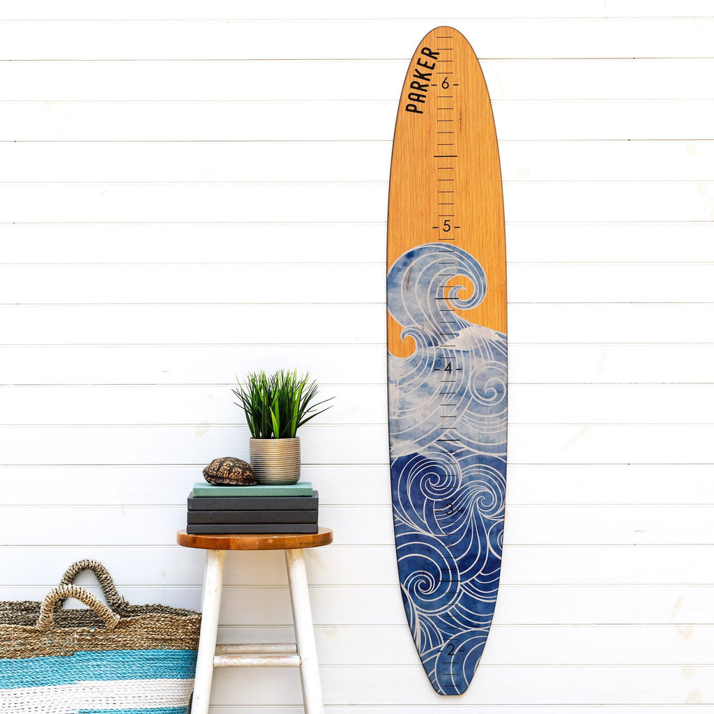 Our wave longboard growth chart makes a great statement piece on this plain wall next to this succulent potted plant and beach tote bag.