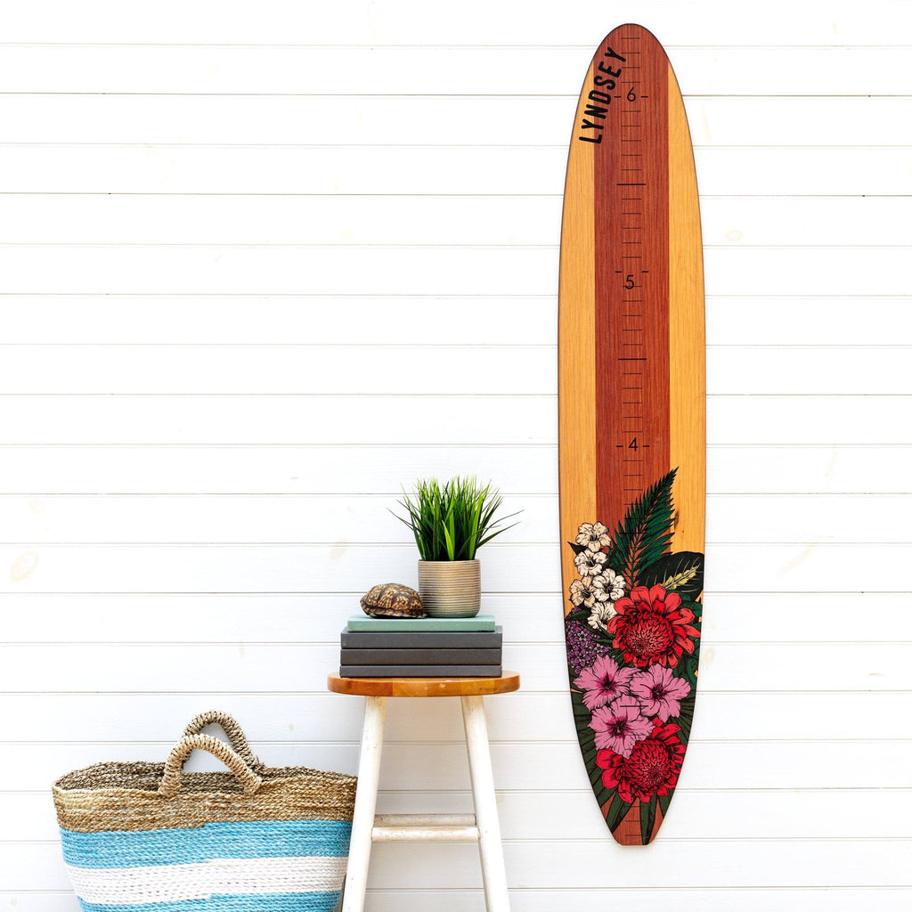 Our floral longboard growth chart makes a great statement piece on this plain wall next to this succulent potted plant and beach tote bag.