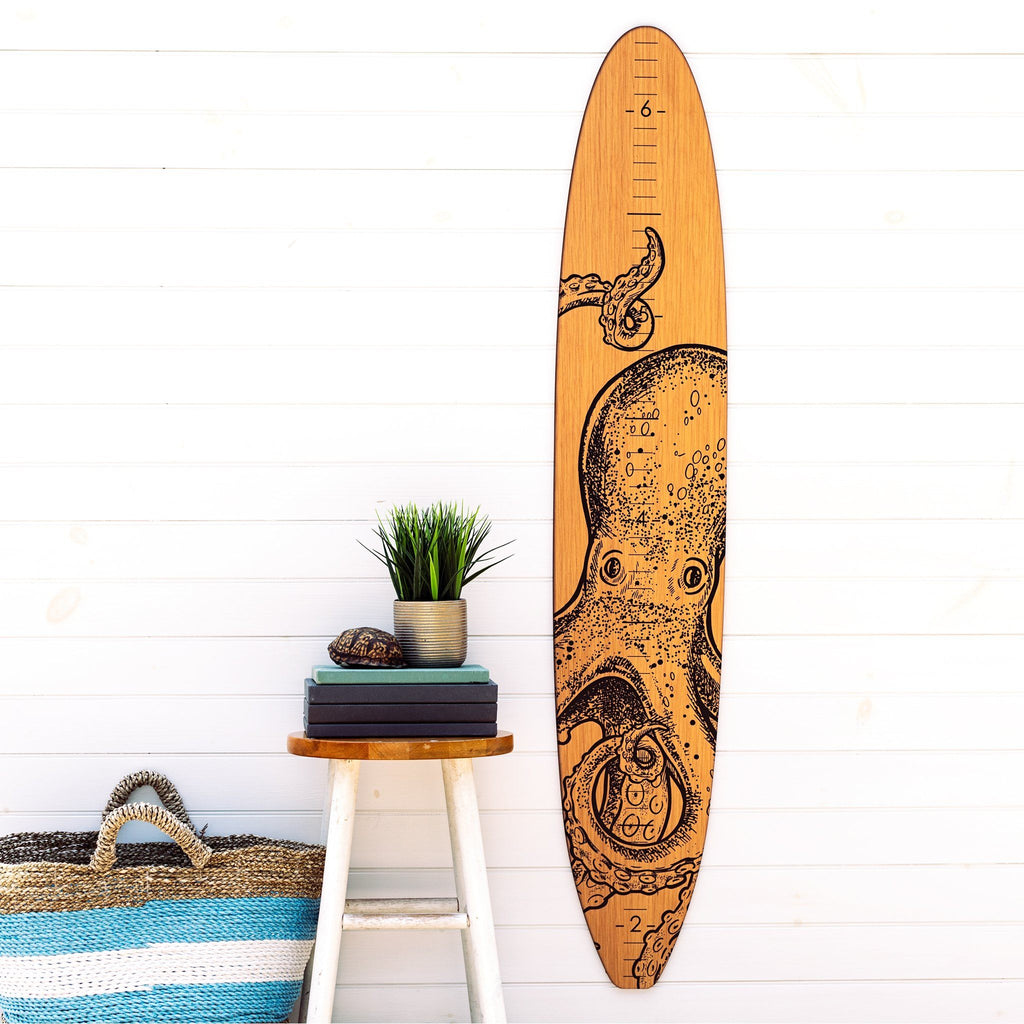 Our octopus longboard growth chart makes a great statement piece on this plain wall next to this succulent potted plant and beach tote bag.
