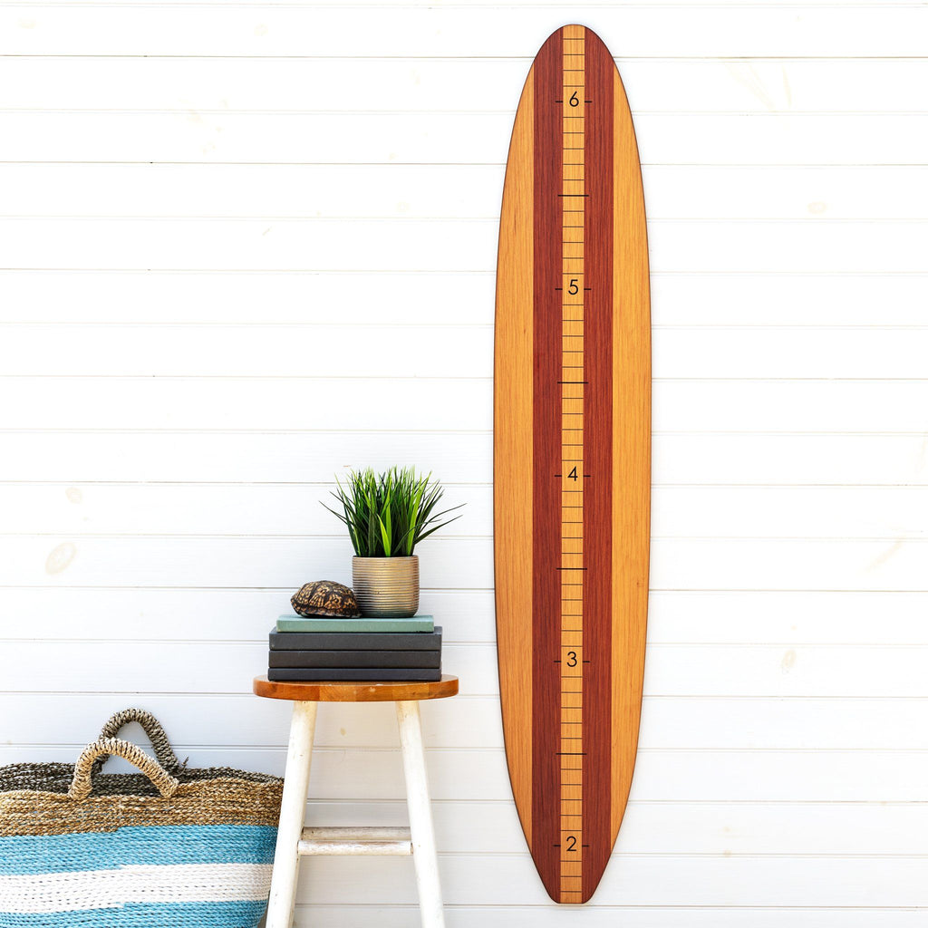 Our wood longboard growth chart makes a great statement piece on this plain wall next to this succulent potted plant and beach tote bag.