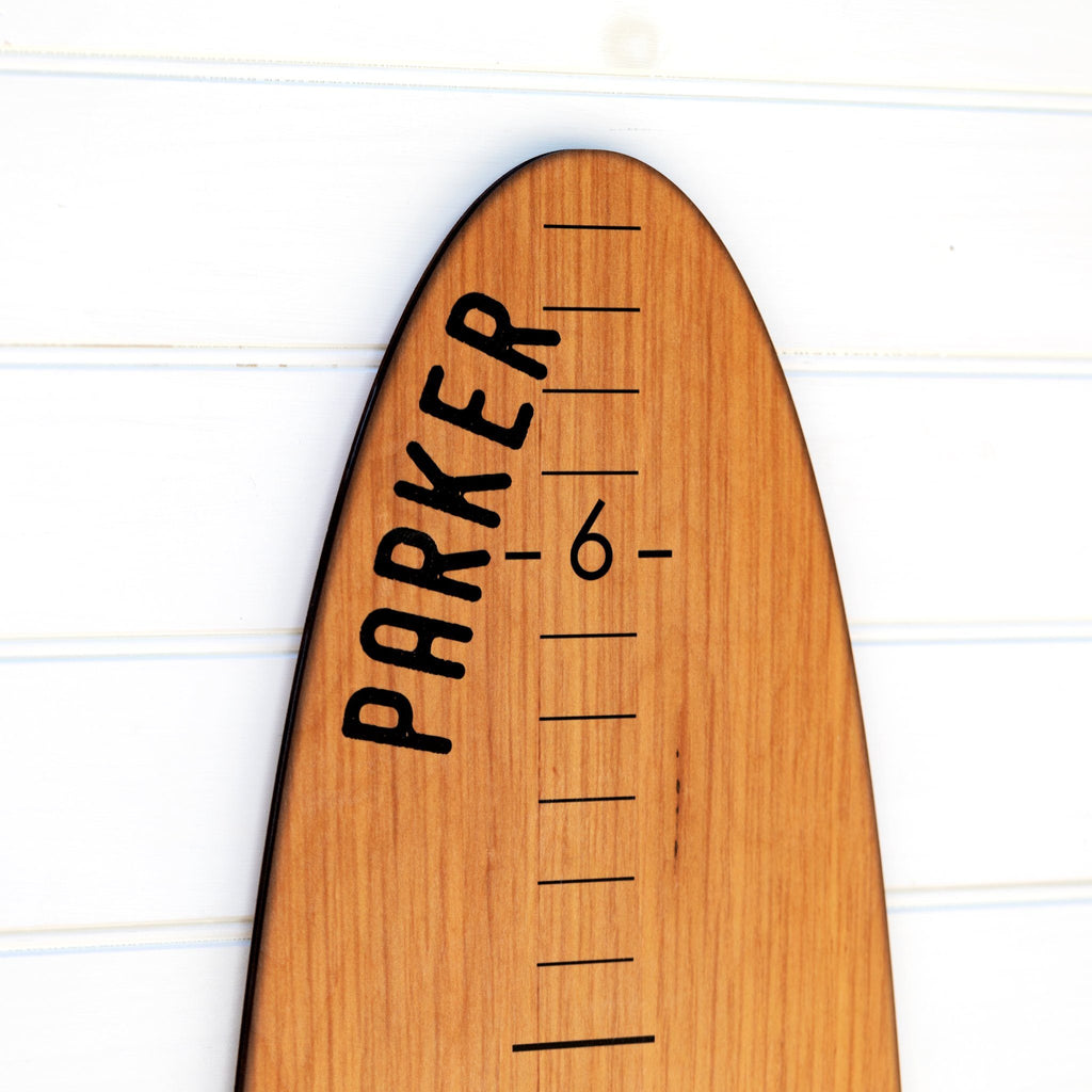 A detailed view of the printed name Parker at the top of our wood longboard growth chart to show how the customization will look.