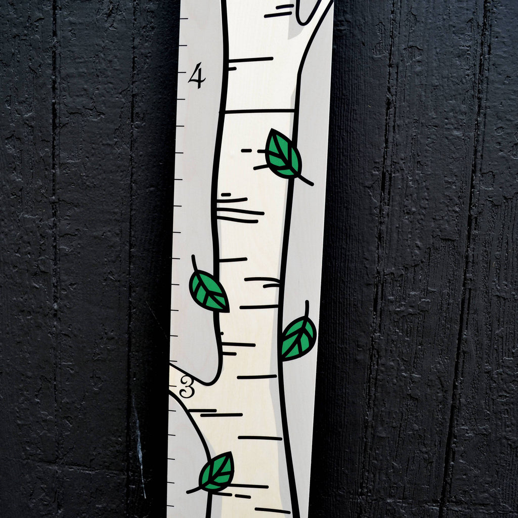 A close-up look at the fun illustrations of the bright green leaves on our birch tree wooden growth chart.