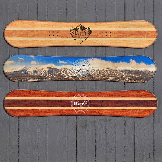 Some of snowboard designs for our alternative wedding guestbook include a blonde wood finish, a bright blue mountain range with skyline and a darker natural wood finish.