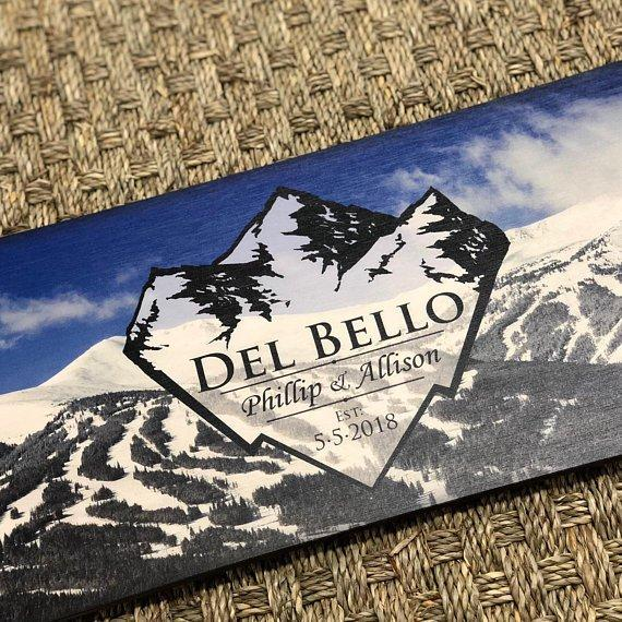 A detailed close-up of a customized logo with the name Del Bello printed on our alternative wedding guest book snowboard with the mountain range as the background.
