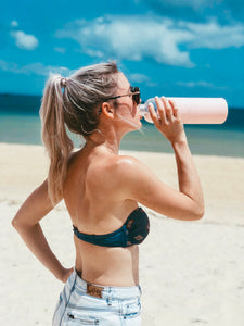 Girl on beach drinking from 1L reusable glass water bottle - Wilfred Eco