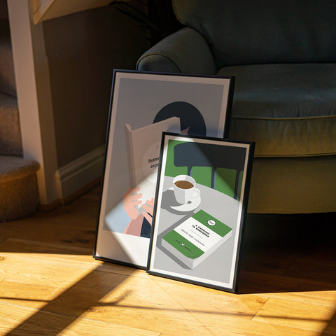 Two prints showing a book and cup of coffee and a man reading a book sit up against an armchair. The sun streams through onto the wooden floor