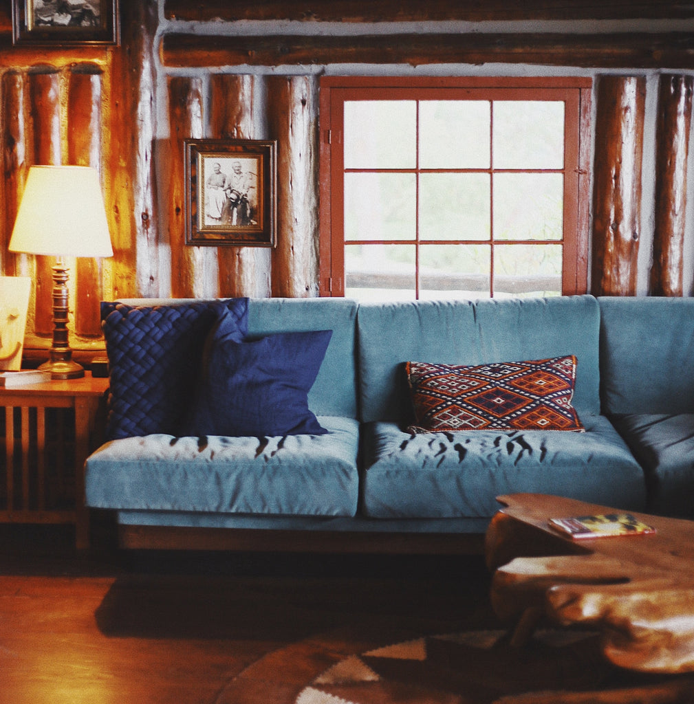 Chalet style living room with wooden walls and features. A light blue velvet sofa and dark blue cushions