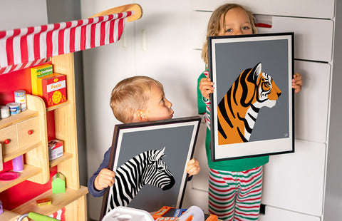 Kids bedroom image with two young boys holding framed prints of a tiger and zebra