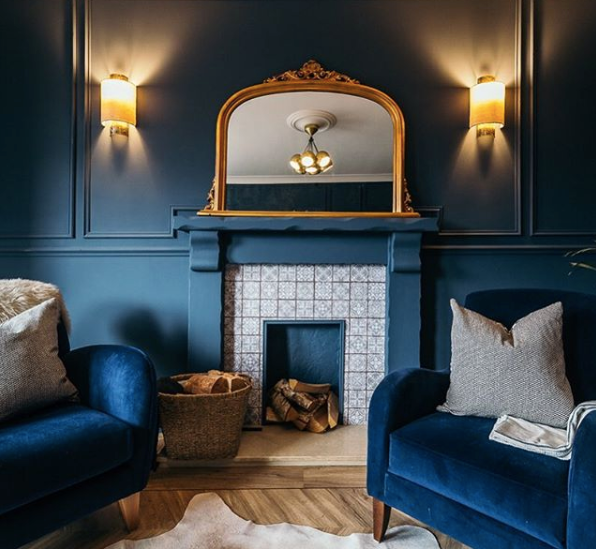 Stunning blue living room showing a fireplace with tiles and blue surround, blue walls with glowing lights and 2 blue velvet armchairs