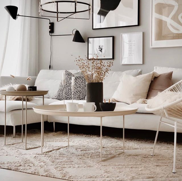 Pared back simple living room decor with neutral walls and sofa, lots of texture and dark accents