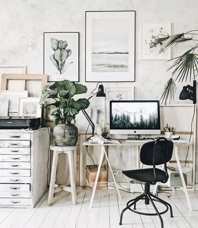 scandi style home office set up with a desk, computer, chair and filing cabinet. Wall art and house plants create a calming productive space