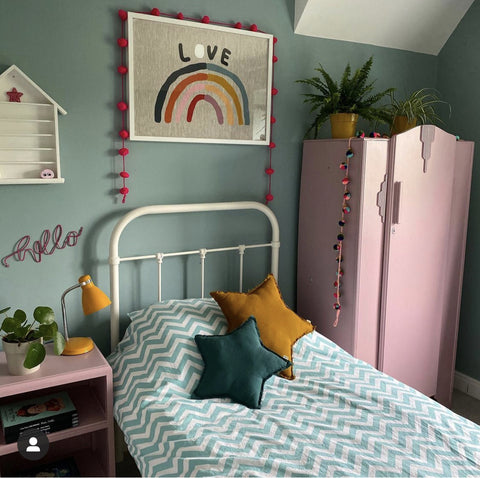 girls bedroom image with a single bed, pink wardrobe, pale green walls and a rainbow art print hung over the bed