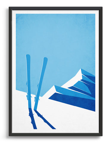 framed art print depicting a snowy mountain top and blue sky with a pair of skis sticking out of the snow