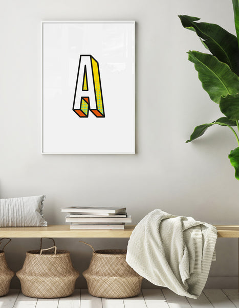 Letter A initial 3D print shown on a neutral colour wall with a wooden bench with seagrass baskets underneath, blankets and books on top and a green plants off to one side