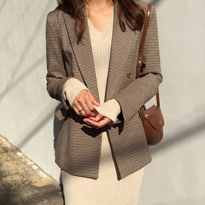 Woman in brown plaid blazer with a tan dress and faux leather purse.