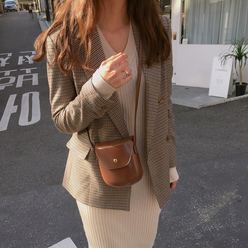 Woman in brown plaid blazer with a tan dress and faux leather purse. Her hand is lifted up and she's wearing a wedding band.