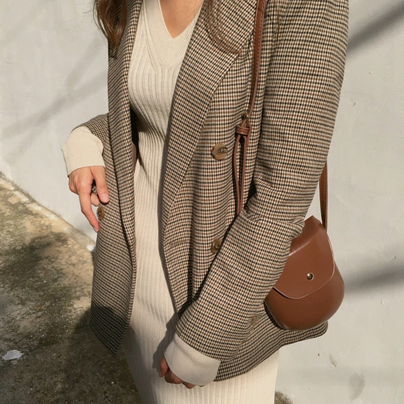 The side of a woman in brown plaid blazer with a tan dress and faux leather purse.