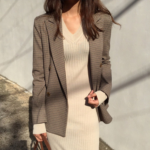 Woman in brown plaid blazer with a tan dress.